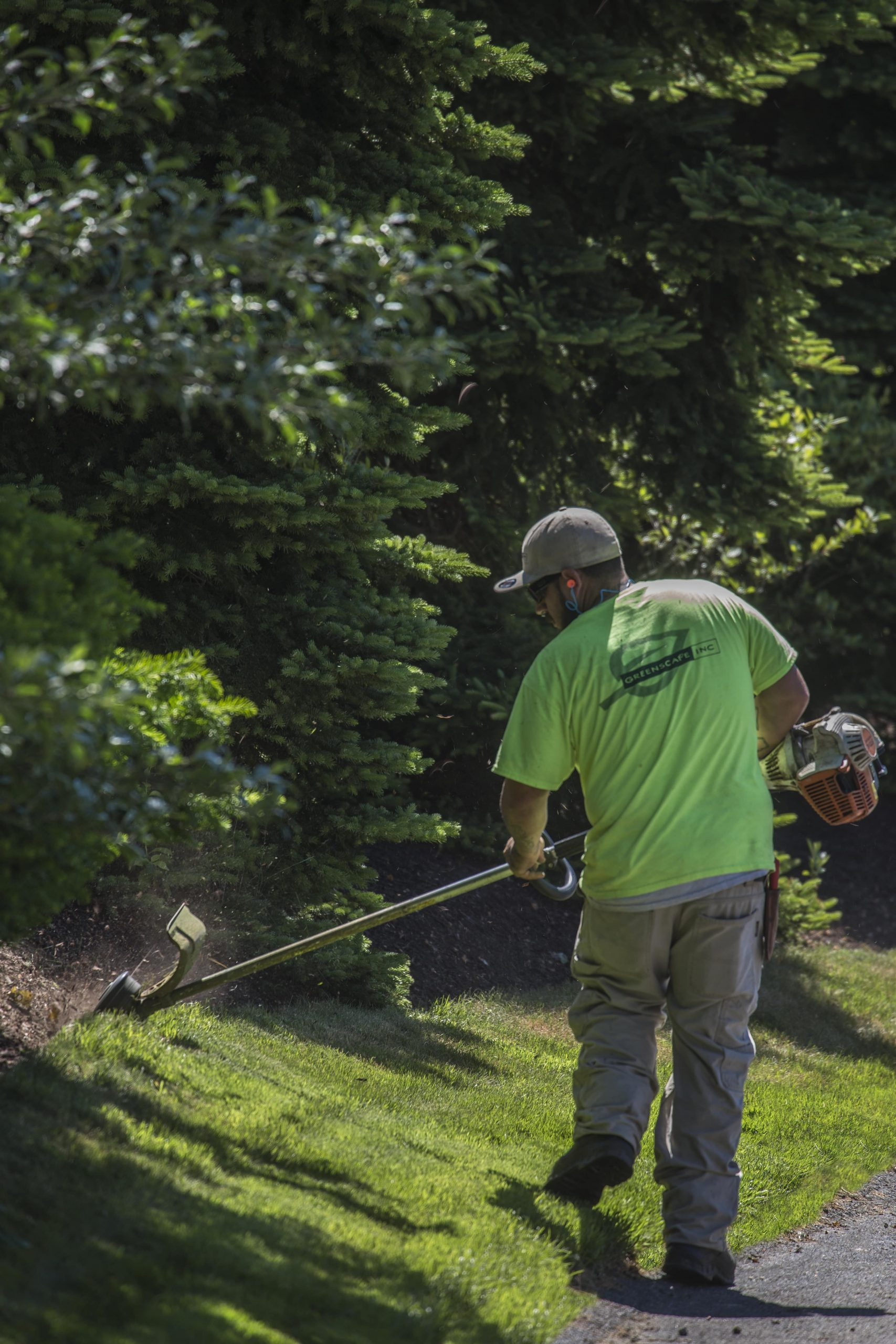 Greenscape employee weed-whacking at Bourne Condos.