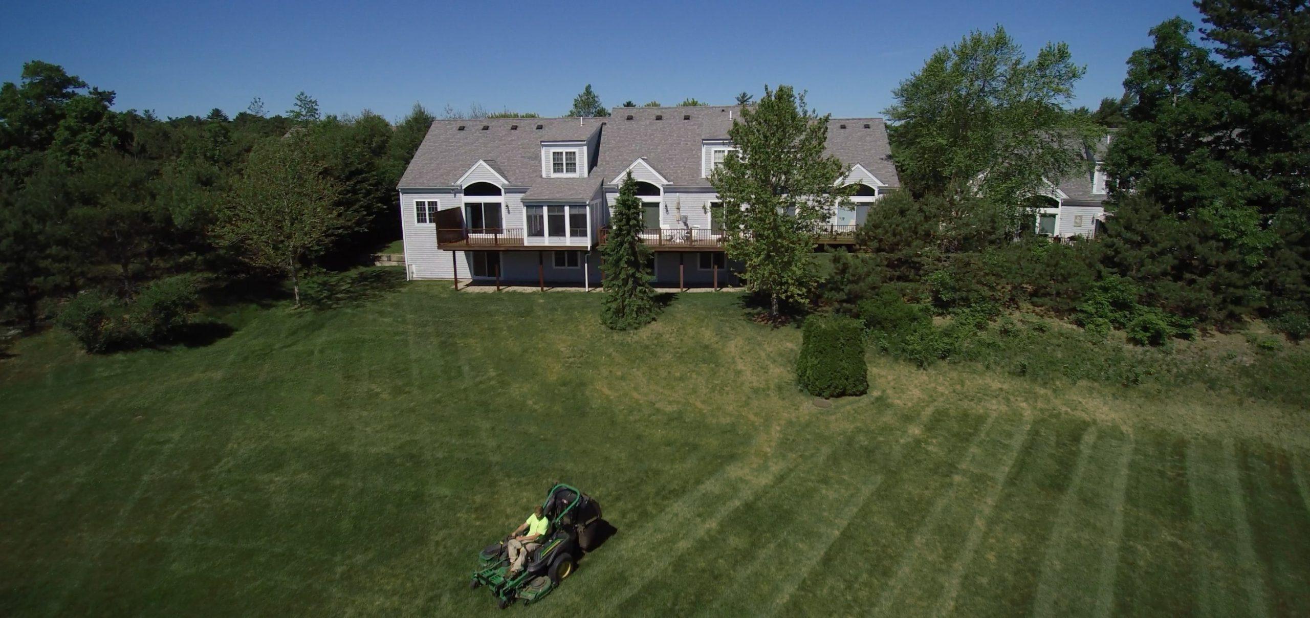 Drone shot of a Greenscape employee mowing at Bourne Condos