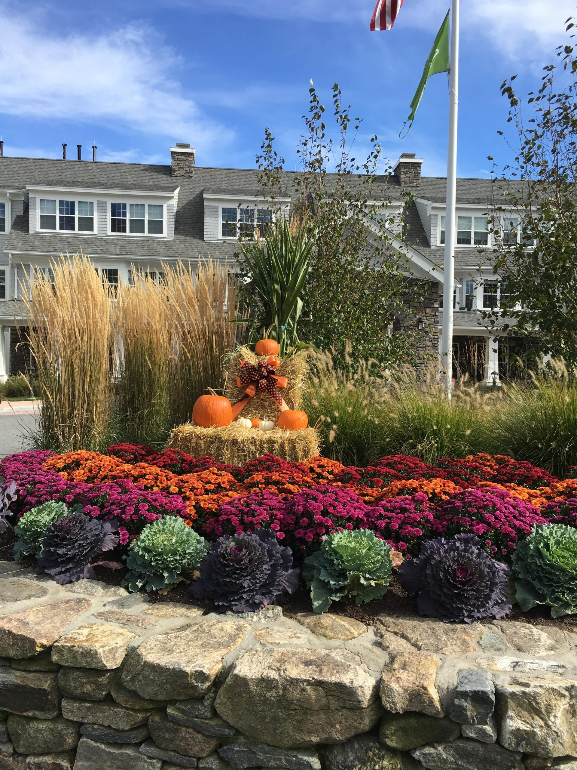 Fall landscaping display complete with pumpkins, flowers, and hay.