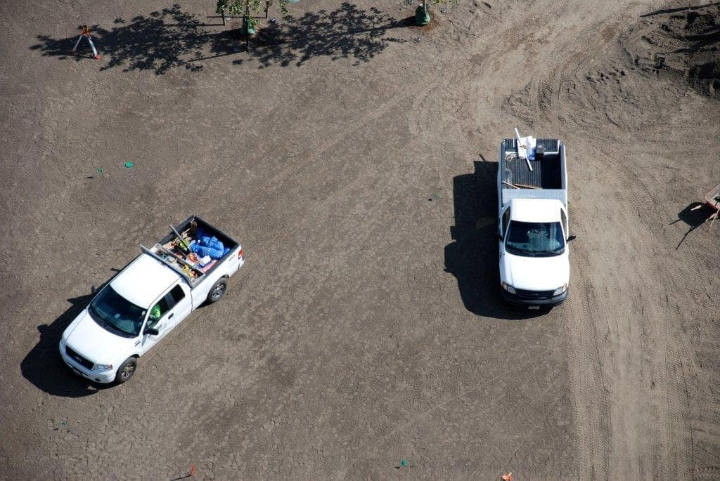 Aerial view of Greenscape trucks on an active job site.