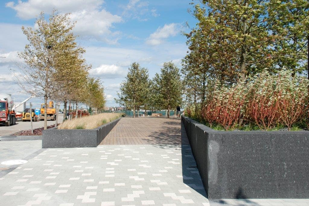 A walkway with plant filled retaining walls on either side.