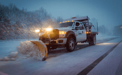 A truck plowing snow during a heavy snowstorm.
